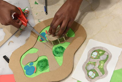 Student's hands working on a mixed media scale model of a community park.
